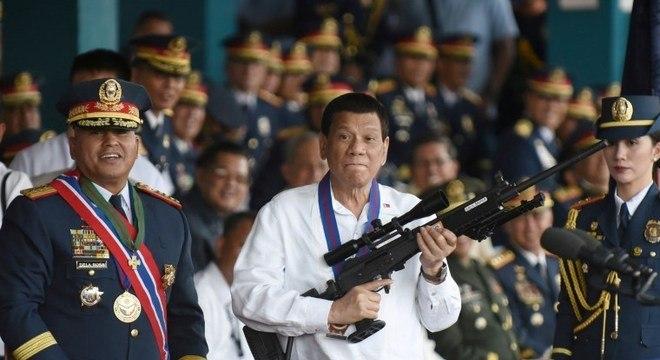 Rodrigo Duterte segura rifle em cerimônia da polícia nacional filipina em abril