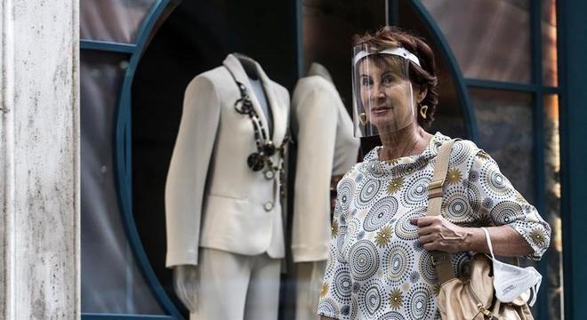 Mulher veste face shield ao andar na rua