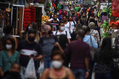 Pessoas com máscaras em rua de comércio popular no Rio