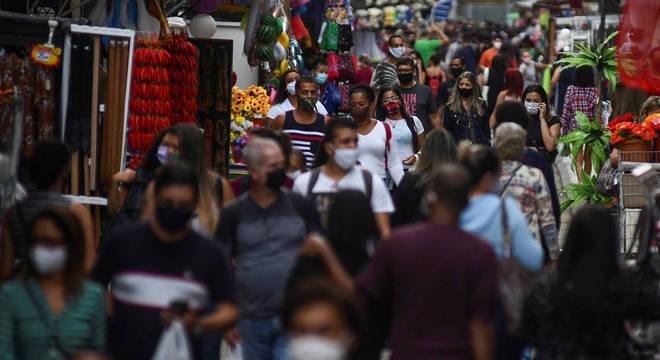 De máscara, populares caminham pelo centro do Rio
