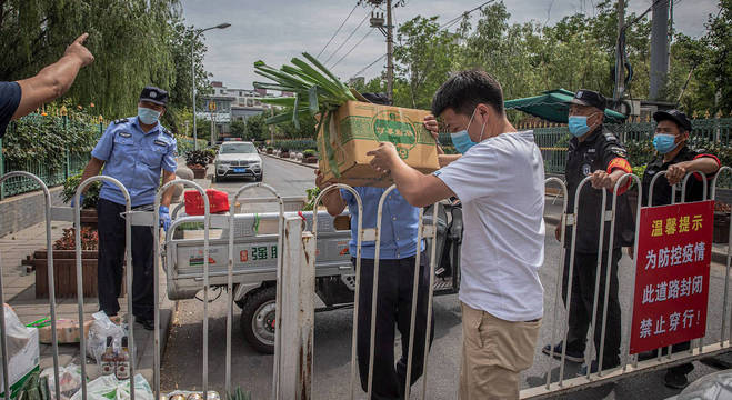 Homem passa caixas de comida para residentes de áreas em lockdown em Pequim