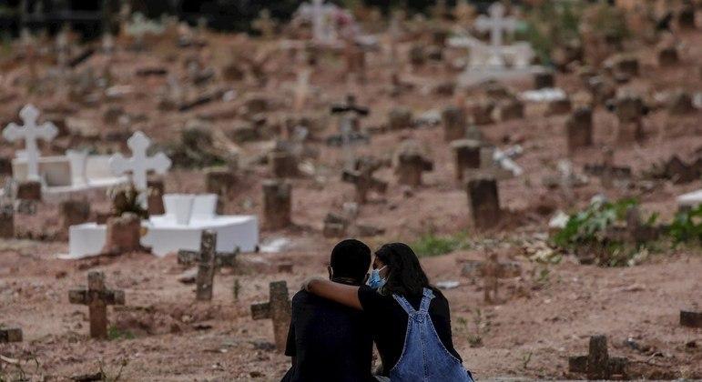 Um casal chorando pela morte de uma mulher, sepultada em um cemitério do Rio de Janeiro