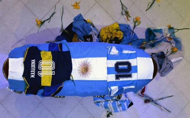 O velório de Diego Maradona acontece nesta quinta-feira (26), na Casa Rosada, sede do governo argentino. Espera-se que mais de 1 milhão de fãs e torcedores passem pelo local para se despedir do ídolo. Muitas pessoas dormiram na Plaza de Mayo para conseguir dar o último adeus ao craque e o governo armou um forte esquema de segurança. No início da manhã, algumas pessoas tentaram forçar a entrada, mas a situação foi controlada pela polícia.