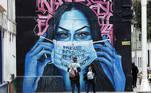 """-FOTODELDÍA- BOG300. BOGOTÁ (COLOMBIA), 02/04/2021.- Dos personas observan un mural que dice """"Insistir, persistir, resistir y nunca desistir"""", hoy, en Bogotá (Colombia). Colombia agregó este viernes 10.222 contagios y otras 163 muertes por coronavirus, cifras por las que las autoridades sanitarias consideran que el país está entrando a una tercera ola de la pandemia. EFE/ Mauricio Dueñas Castañeda"""