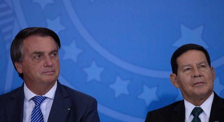 O vice-presidente Hamilton Mourão (à direita) ao lado de Bolsonaro; disputa ao Senado ou concorrer à reeleição com o presidente estão entre as possibilidades para 2022