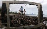 -FOTODELDIA- Banda Aceh (Indonesia), 02/06/2021.- Un hombre y dos niños camina entre la basura que cubre la playa de Kampung Jawa en Banda Aceh (Indonesia) este miércoles. EFE/Hotli Simanjuntak