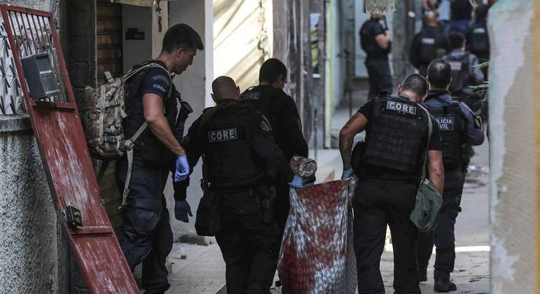 Policiais do Core carregam corpo durante operação policial no Jacarezinho
