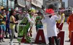 AME411. LA PAZ (BOLIVIA), 05/07/2021.- Un grupo de payasos ameniza hoy en una de las filas para recibir la vacuna contra la covid-19, mientras esperaban su turno con jeringas gigantes, vestidos de doctores y con mascarillas con grandes sonrisas, en La Paz (Bolivia). Desde que se inició la vacunación a finales de enero en el país ya se han vacunado a 2.762.994 personas entre la primera y segunda dosis con las vacunas Sputnik V, AstraZeneca, Sinopharm y Pfizer. Bolivia ha acumulado 444.968 contagios y 16.951 fallecidos desde que en marzo de 2020 se detectaron los primeros casos. EFE/ Martin Alipaz