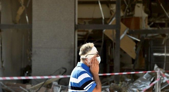 Homem ferido caminha em frente a prédios destruídos pela explosão em Beirute