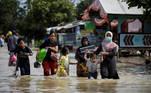 -FOTODELDÍA- Bekasi (Indonesia), 22/02/2021.- Varias personas cargan con sus pertenencias mientras atraviesan una zona anegada debido a una inundación en Pebayuran, Bekasi, Indonesia, el 22 de febrero se 2021. Las fuertes lluvias dañaron el terraplén del río Citarum, que han causado la inundación de miles de casas y la huída de miles de personas. EFE/EPA/MAST IRHAM