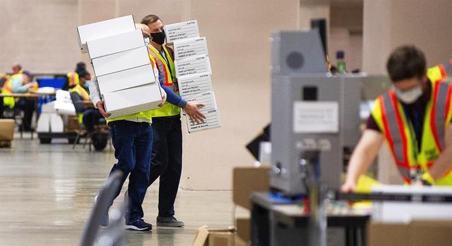 Funcionários carregam caixas com votos em centro de apuração na Filadélfia
