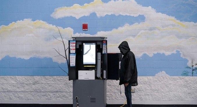 Eleitor deposita seu voto para o Senado em uma urna em Atlanta