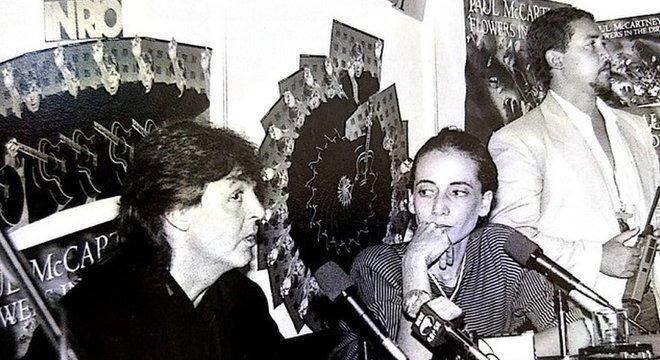 Em foto preto e branco, Paul McCartney fala no microfone, observado por May Waddington