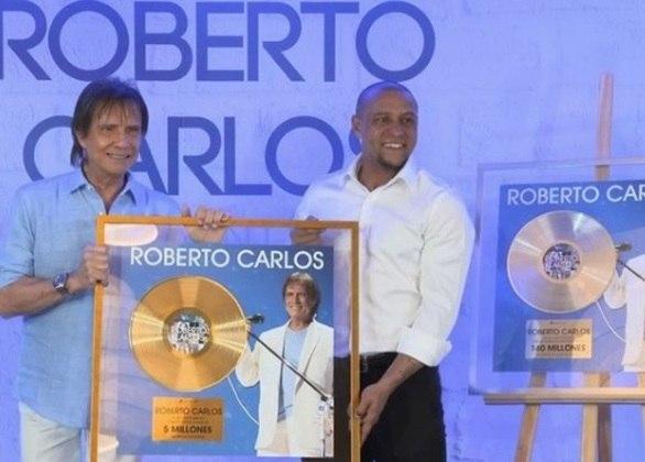 Em sua turnê pelo exterior, em 2019, o cantor Roberto Carlos teve o que comemorar e... ao lado de um astro do esporte. Em evento em Madri, o ex-lateral ROBERTO CARLOS entregou ao xará dois discos emblemáticos. Em um deles, a gravadora Sony Music celebrou a venda de 5 milhões de discos do cantor RC na Espanha. No outro, os mais de 140 milhões de discos comercializados por toda a América Latina.