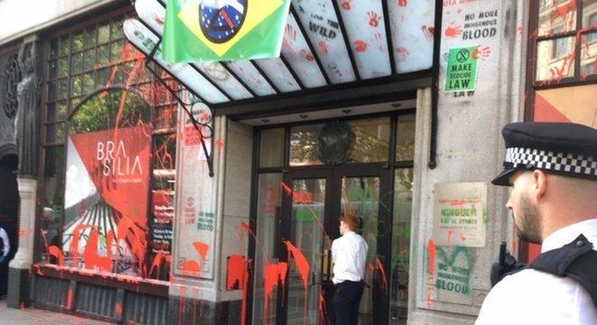 Manifestantes picharam a fachada da embaixada brasileira com tinta vermelha, simbolizando o 'sangue derramado', dos indígenas; rapaz está 'colado' à porta