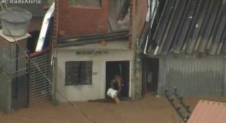 Morador usa balde para retirar lama de dentro de casa
