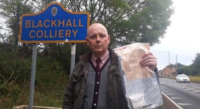 Detetive John Forster mostra envelope encontrado com dinheiro em Blackhall