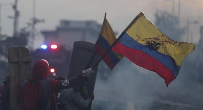 Manifestantes com a bandeira do Equador durante confronto com a polícia