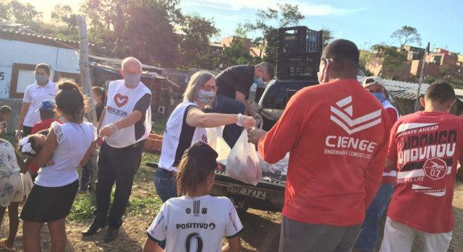 Voluntários distribuem os alimentos para famílias que precisam de ajuda