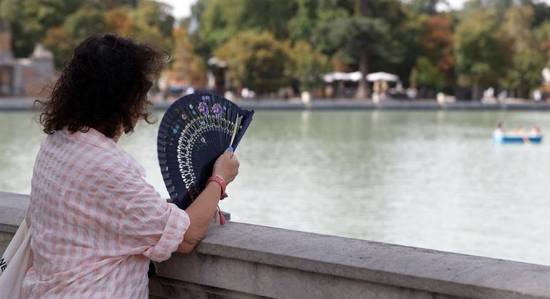 Mulher usa leque para se abanar no parque do Retiro, em Madri, capital da Espanha