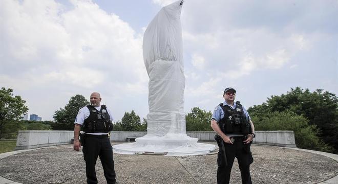 Estátua de Cristovão Colombo coberta e protegida por policiais nos EUA