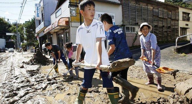 Estudantes e moradores removem lama depois de enchentes causadas por tufão Hagibis