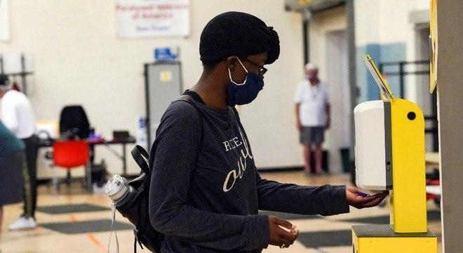 Eleitora higieniza as mãos após depositar seu voto antecipado em Houston