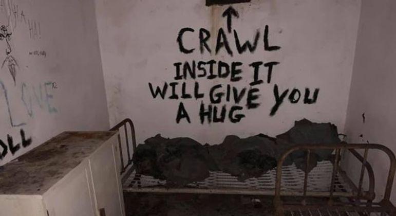 'Rastejo para dentro isso vai lhe dar uma abraço [sic]', diz a mensagem na parede