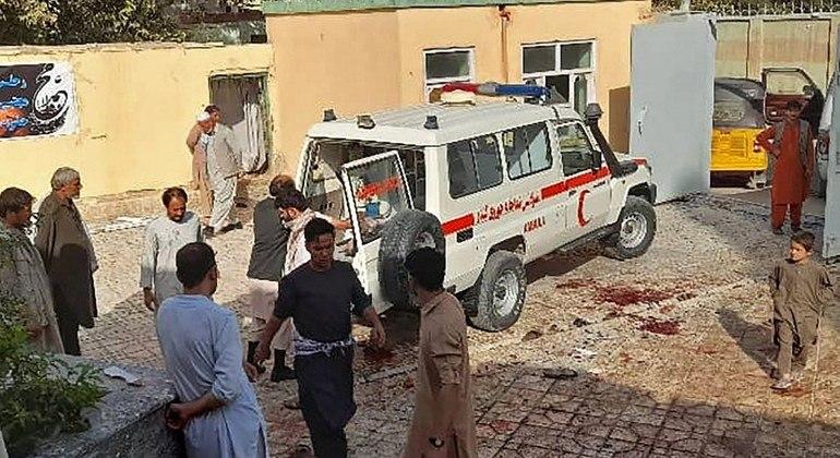 Homens afegãos permanecem ao lado de uma ambulância após um ataque a bomba em uma mesquita em Kunduz