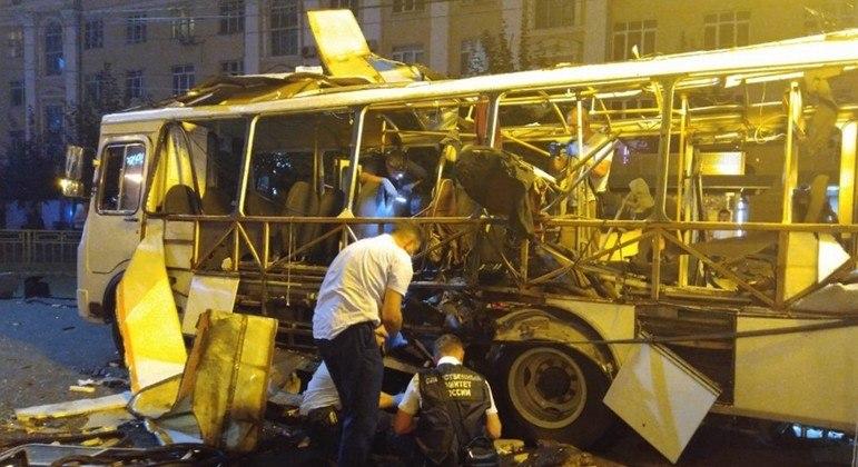 Policiais examinam a carcaça do ônibus que explodiu no sudoeste da Rússia