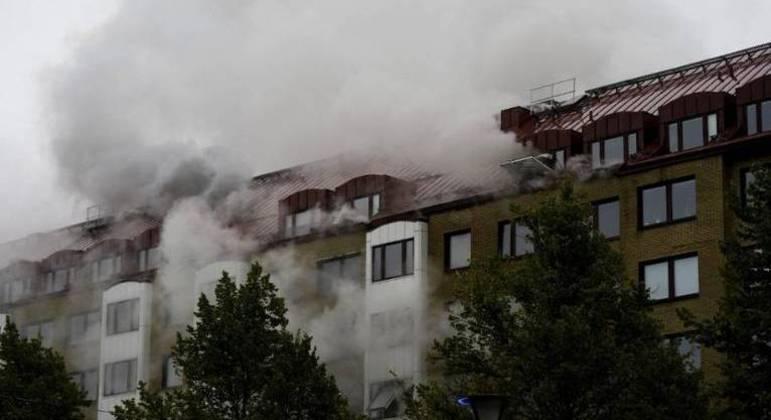 Fumaça sai de um prédio enquanto serviços de emergência combatem incêndio no local da explosão que ocorreu  em  Gotemburgo