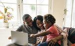 Família sentada diante de computador.