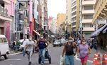 Na rua 25 de março, o movimento é intenso nesta segunda e algumas lojas abriram, mesmo com as restrições. Vendedores tentavam levar compradores em estabelecimentos com as portas aparentemente fechadas