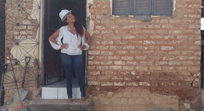 Fernanda Silmara Silva dos Santos em frente à casa que ajudou a reformar em projeto voluntário