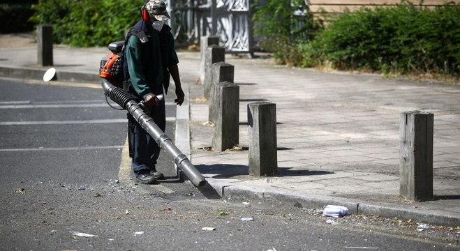 Trabalhador da limpeza urbana recolhe detritos da festa de rua em Brixton