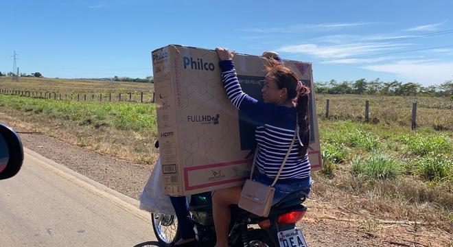 Mulher se arrisca na garupa de moto sem capacete e equilibrando um televisor