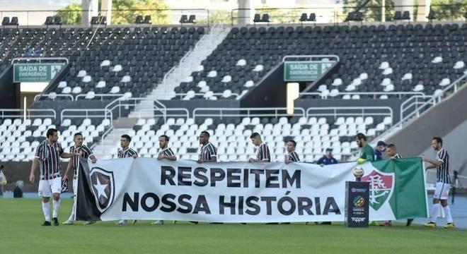 Jogadores entram com faixa de protesto no gramado do Engenhão