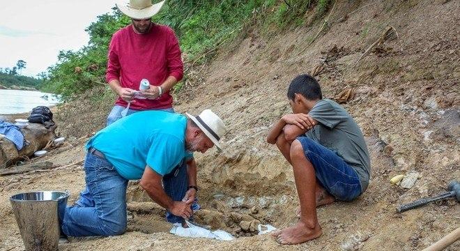 Paleontólogo Jonas Filho retirando o fóssil do Purussauro próximo ao Rio Acre
