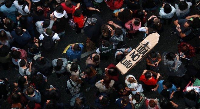 Foto aérea mostra dezenas de manifestantes em avenida de São Paulo, com caixa de papelão em formato de caixão dizendo: