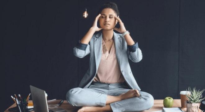 Fotografia de mulher meditando no ambiente de trabalho para ilustração do item