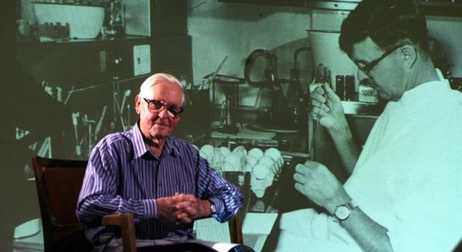 O professor Frank Fenner em frente a uma foto projetada de si mesmo, tirada na década de 1950