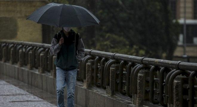 Pessoas se protegem da chuva e frio intenso na tarde desta sexta-feira (21), em SP