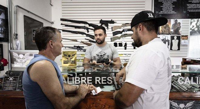 Funcionário do clube de tiro 1911 mostra pistola a clientes