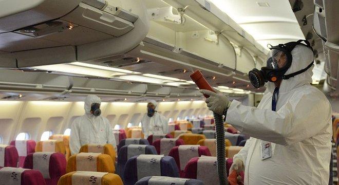 Funcionários aplicam solução antisséptica em avião na Tailândia, em 2015, como prevenção à síndrome respiratória Mers