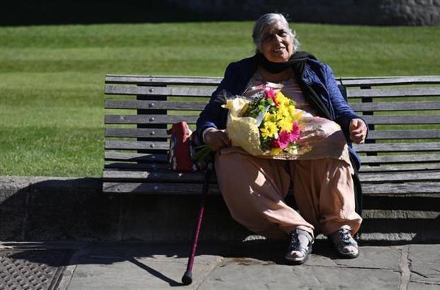 Algumas pessoas também prestaram homenagens. Nesta foto, uma senhora que não foi identificada segura um buquê de flores do lado de fora do Castelo de Windsor