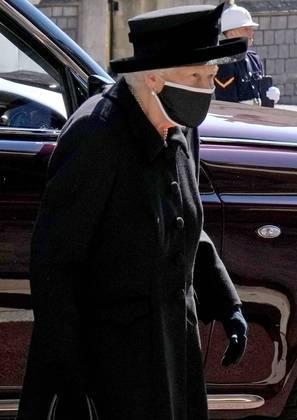 A monarca estava usando roupa e chapéu pretos e duas máscaras
