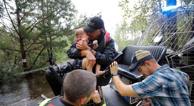 Socorrista conforta bebê resgatado de inundação provocada pelo furacão Florence