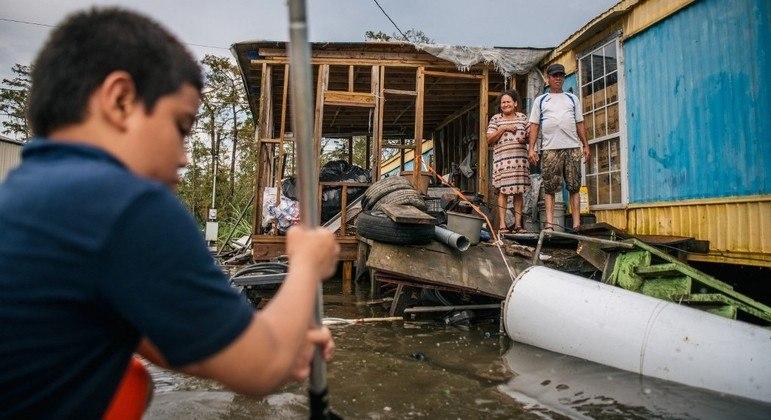 Família utiliza barco para sair de casa após passagem do furacão Ida pelos EUA