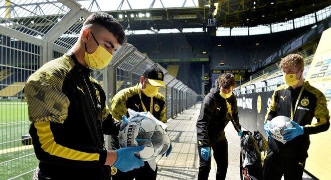 Gandulas, com máscaras, desinfetam as bolas, antes do jogo