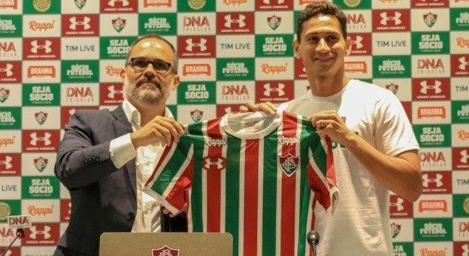 O meia Ganso (à dir.) segura camisa do Fluminense durante sua apresentação